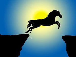 Horse silhouette leaping over a canyon must be focused to assure a safe landing